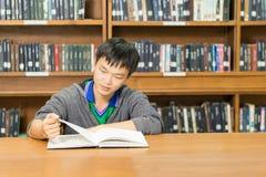 Ritratto di giovane studente serio che legge un libro in una biblioteca Fotografia Stock