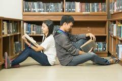 Ritratto di giovane studente serio che legge un libro in una biblioteca Fotografie Stock Libere da Diritti