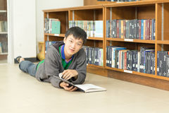Ritratto di giovane studente serio che legge un libro in una biblioteca Fotografie Stock