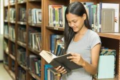 Ritratto di giovane studente serio che legge un libro in una biblioteca Fotografia Stock Libera da Diritti