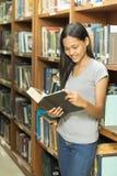 Ritratto di giovane studente serio che legge un libro in una biblioteca Immagine Stock Libera da Diritti