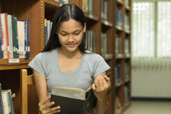 Ritratto di giovane studente serio che legge un libro in una biblioteca Immagine Stock