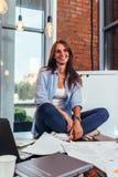 Ritratto di giovane studente sorridente che si siede sulla tavola coperta in carte nella posa del loto che prepara per l'esame ne Immagine Stock Libera da Diritti