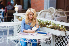 Ritratto di giovane studentessa astuta con il libro di lettura dei capelli biondi prima dell'inizio le sue conferenze in universi Immagini Stock Libere da Diritti