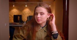 Ritratto di giovane studentessa che si siede seducente in orologi dell'ufficio nella macchina fotografica video d archivio