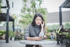 Ritratto di giovane telefono cellulare di uso della donna di affari mentre sedendosi i fotografia stock