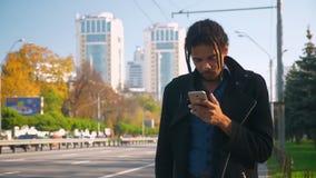 Ritratto di giovane tipo afroamericano con i dreadlocks che guarda nello smartphone e che guarda nervoso fuori nella strada stock footage
