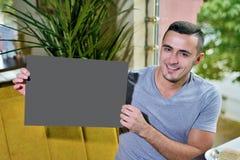 Ritratto di giovane tipo in caffè l'uomo tiene in sue mani una tavola vuota per testo fotografia stock