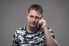 Ritratto di giovane uomo adulto bello che parla sul telefono cellulare e che sorride esaminando macchina fotografica immagine stock