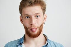 Ritratto di giovane uomo allegro che esamina macchina fotografica che mostra lingua sopra fondo bianco Fotografia Stock Libera da Diritti