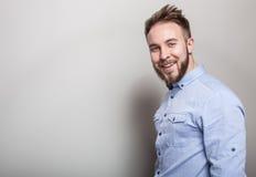 Ritratto di giovane uomo amichevole bello in camicia blu Foto dello studio su fondo grigio chiaro Fotografia Stock Libera da Diritti