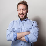 Ritratto di giovane uomo amichevole bello in camicia blu Foto dello studio su fondo grigio chiaro Immagine Stock Libera da Diritti
