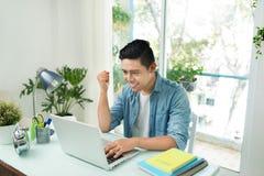 Ritratto di giovane uomo asiatico emozionante di affari che lavora al computer portatile c Fotografie Stock Libere da Diritti