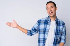 Ritratto di giovane uomo asiatico felice dei pantaloni a vita bassa che mostra qualcosa fotografia stock libera da diritti