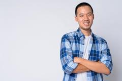 Ritratto di giovane uomo asiatico felice dei pantaloni a vita bassa che sorride con le armi attraversate immagine stock