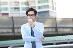 Ritratto di giovane uomo asiatico sicuro di affari che esamina Smart Phone mobile l'ufficio esterno immagine stock
