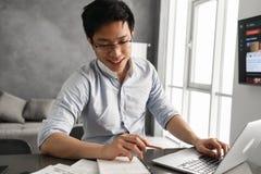 Ritratto di giovane uomo asiatico sorridente che per mezzo del computer portatile Fotografia Stock Libera da Diritti