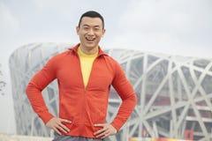 Ritratto di giovane uomo atletico sorridente in parco, esaminante macchina fotografica, con costruzione moderna nei precedenti a P Fotografia Stock Libera da Diritti