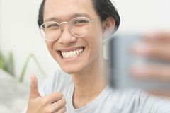 Ritratto di giovane uomo attraente che prende ad immagini di lui auto o selfie mentre le elasticità sfogliano su immagine stock libera da diritti