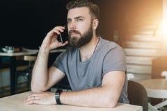 Ritratto di giovane uomo barbuto bello dei pantaloni a vita bassa che si siede in caffè alla tavola e che parla sul suo telefono  Immagini Stock Libere da Diritti