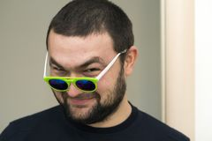 Ritratto di giovane uomo barbuto bello divertente in vetri verdi Fotografia Stock Libera da Diritti