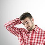 Ritratto di giovane uomo barbuto confuso che guarda giù fotografia stock