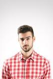 Ritratto di giovane uomo barbuto scettico Fotografia Stock