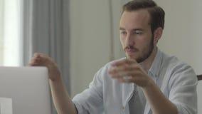 Ritratto di giovane uomo bello che rompe matita con rabbia che si siede davanti al suo computer nell'ufficio Problemi a archivi video