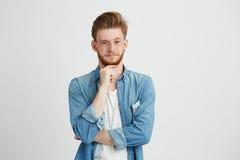 Ritratto di giovane uomo bello sicuro con la barba che esamina macchina fotografica che pensa con la mano sul mento sopra fondo b Fotografia Stock