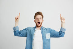Ritratto di giovane uomo bello sorpreso che esamina macchina fotografica con la bocca aperta che indica dito su sopra fondo bianc Immagini Stock Libere da Diritti