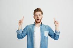 Ritratto di giovane uomo bello sorpreso che esamina macchina fotografica con la bocca aperta che indica dito su sopra fondo bianc Fotografie Stock Libere da Diritti