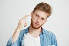 Ritratto di giovane uomo brutale con la barba che esamina macchina fotografica che fa la pistola della mano sopra fondo bianco Fotografia Stock