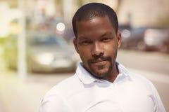 Ritratto di giovane uomo d'affari afroamericano sicuro felice nell'usura convenzionale su fondo vago immagine stock libera da diritti