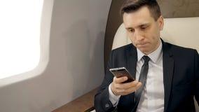 Ritratto di giovane uomo d'affari bello facendo uso dello smartphone che si siede nella prima classe dell'aeroplano video d archivio