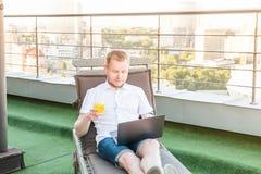 Ritratto di giovane uomo d'affari con la bevanda che lavora al computer portatile che si siede confortevolmente sulla sedia a sdr fotografie stock