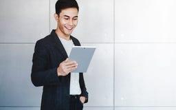 Ritratto di giovane uomo d'affari felice Using Digital Tablet Fare una pausa il muro di cemento industriale fotografia stock