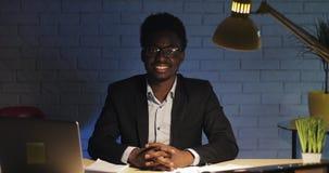Ritratto di giovane uomo d'affari nero felice che si siede alla tavola nei precedenti dell'ufficio alla notte e che esamina archivi video