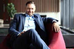 Ritratto di giovane uomo d'affari positivo che si siede in un ambiente corporativo moderno, esaminante la macchina fotografica immagini stock