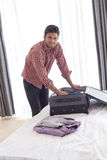Ritratto di giovane uomo d'affari sicuro che disimballa valigia sul letto Fotografia Stock