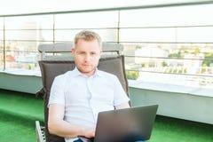 Ritratto di giovane uomo d'affari sorridente che lavora al computer portatile che si siede confortevolmente sulla sedia a sdraio  immagine stock