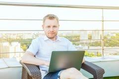 Ritratto di giovane uomo d'affari sorridente che lavora al computer portatile che si siede sulla sedia sul balcone del terrazzo d fotografia stock