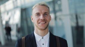 Ritratto di giovane uomo d'affari sorridente con la condizione dello zaino fuori dell'aeroporto e esaminare la macchina fotografi stock footage