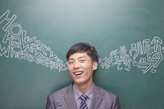 Ritratto di giovane uomo d'affari sorridente davanti al bordo nero con lo scritto cinese ed inglese che viene da ogni orecchio Fotografie Stock