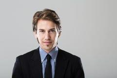 Ritratto di giovane uomo d'affari su fondo grigio immagine stock