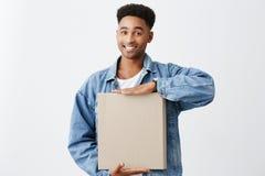Ritratto di giovane uomo dalla carnagione scura attraente allegro con l'acconciatura di afro in carta bianca della tenuta della g immagine stock