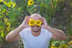 Ritratto di giovane uomo felice che sorride e che si siede su un giacimento di fiore del sole fotografia stock