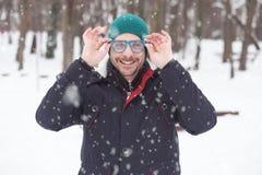 Ritratto di giovane uomo felice con gli occhiali da sole blu ed il cappello verde o immagini stock