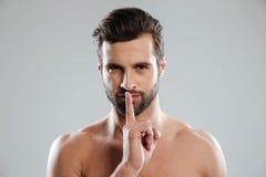 Ritratto di giovane uomo nudo affascinante che mostra gesto di silenzio Fotografia Stock