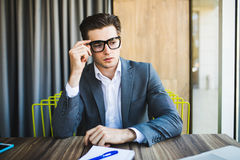 Ritratto di giovane uomo occupato di che pensa al compito in ufficio Immagine Stock
