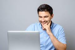 Ritratto di giovane uomo sorridente che si siede allo scrittorio con il computer portatile Fotografie Stock Libere da Diritti